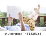 young man reading a book lying... | Shutterstock . vector #451525165