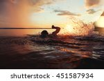 Athletic man is trained to swim in a lake at sunset. It flies a lot of water splashing. Vintage color - stock photo