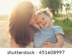 Mother Kissing Toddler Girl In...