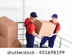 two male workers with boxes on... | Shutterstock . vector #451698199