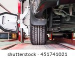 Small photo of tire clamped with aligner undergoing auto wheel alignment