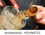 whiskey shot mid pour | Shutterstock . vector #451966711