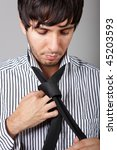 young person in a striped shirt binding a black necktie - stock photo