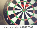Small photo of Darts accurately and perfectly hit the winning red spot on board (Focus on tip of the dart) - indicates right targeting, marketing, focus concept.