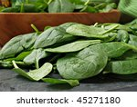 Freshly washed baby spinach leaves on slate cutting board with salad bowl in background.  Macro with shallow dof. - stock photo