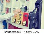 Small photo of Woman hand swiping credit card at gas pump station.