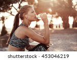Thirsty Female Jogger Drinking...