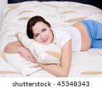 Beautiful brunette pregnant woman lying on the sofa - stock photo