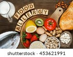 Small photo of Allergy food concept. Allergy food as almonds, milk, pistachios, tomato, lemon, kiwi, trout, strawberry, bread, sesame seeds, eggs, peanuts and bean on wooden table