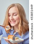 happy young blond woman eating... | Shutterstock . vector #453851449