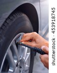Small photo of checking air pressure and refilling air into car tire at petrol station.