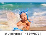 Small photo of Concept summer toady sea, ocean, travel. Beautiful young girl on the beach wearing a scuba diving lying on the beach, beautiful splashes of water.