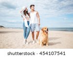 Stock photo happy young couple walking with dog on the beach in summer 454107541