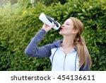 sporty woman drinking water... | Shutterstock . vector #454136611