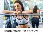 fit woman in a gym looking at... | Shutterstock . vector #454275991