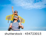 Small photo of Kid with jet pack pretend to be superhero. Child playing with father in summer. Happy dad and son outdoors. Success, leader and winner concept