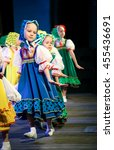Small photo of Girls in Slavic costumes and scarves on their heads dancing folk dance on stage. Coquetry and modesty - Russia, Abakan, choreography Festival, October 25, 2015