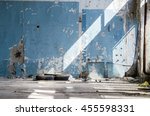 Small photo of Inside An Old Abandoned Industrial Building, Factory. The Wall With Peeling Blue Paint. Used Tires, Wheels. Many Different Garbage. Broken Glass Unit.