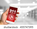 Small photo of Woman hand holding smartphone against blur bokeh of building background 911 Emergency concept