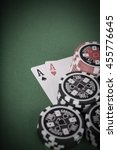 Small photo of photo of aces pair, red and black casino chips on green table - vintage
