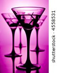 four glasses of martini on purple background, shallow depth of field - stock photo
