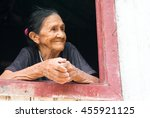 Small photo of Boca de Valeria, Brazil - December 03, 2015: old mature mulatto woman with kind smiling face holding hands together standing in wooden window brown and white color looking outdoor