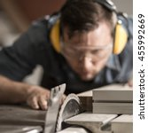 Small photo of Portrait of accurate joiner sawing wood using electric saw
