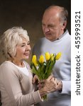 Small photo of Affectionate portrait of a senior man giving flowers to his beloved wife