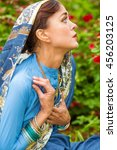 Small photo of Middle age sad woman in blue sari and Indian adornment poses in garden