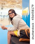 Small photo of Air travel concept. Young casual woman on smart phone at gate waiting in terminal sitting with hand luggage