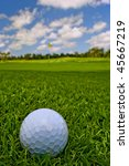 golf ball lies in grass turf near green - stock photo