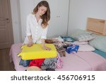 young woman collects a suitcase ... | Shutterstock . vector #456706915