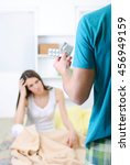 Small photo of Young man showing a woman a condom and pills for headaches while she abide head