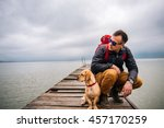 Man With His Dog Sitting On Dock