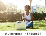 Happy and cheerful black female with short haircut sitting on the grass, smiling to her friends approaching her. Young African student using her notebook outdoor, resting after a hard day at college