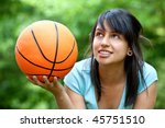 Girl holding a basketball at the park - stock photo