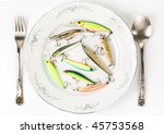 Porcelain plate with plastic fishing lures isolated on white. Artificial food concept or just fishing theme. - stock photo