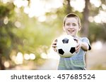 a kid holding up his soccer ball | Shutterstock . vector #457685524