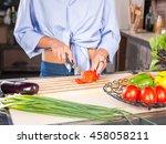 woman slicing tomato on kitchen | Shutterstock . vector #458058211