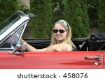 young blonde lady behind the steering wheel of a red antique convertible sports car