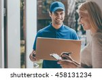 Small photo of Signing to get her package. Smiling young delivery man holding a cardboard box while beautiful young woman putting signature in clipboard