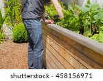 man working on a raised bed in... | Shutterstock . vector #458156971