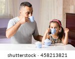 Little Girl is Serving Tea To Her Father With Her Toys - stock photo