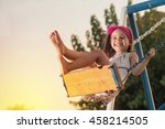 Little girl is swinging at play ground when sun is setting. - stock photo