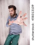 Small photo of funny guy hipster bewhiskered. Gay men on the floor freak. heavy beard. Funny emotions on the man's face.