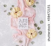 """Small photo of inspirational quote """"the greater your storm the brighter your rainbow"""" written in calligraphy Flat lay style on paper with dry white tulips, eucalyptus petals and pink textile on concrete background."""