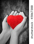 red heart in hands on dark background - stock photo