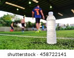 Stock photo water sport drink against blurred soccer background on green artificial grass 458722141
