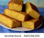Stock photo cornbread squares stacked on a white plate closeup on a blue background 460106104