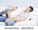 Young couple recline on a white sofa with the young woman lying on the man with a pillow. Horizontal shot. - stock photo